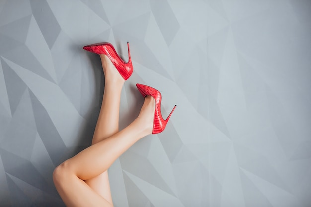 Female long legs in red high heels on a light grey . fashion .