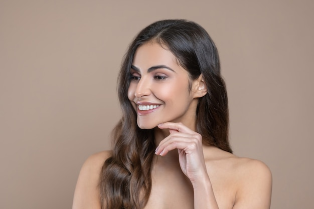 Female look. pretty smiling woman looking to side touching her finger to chin indoors