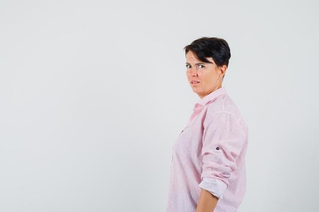 Женщина смотрит в камеру в розовой рубашке и выглядит высокомерно. .