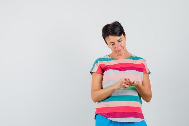 Женщина смотрит на ее открытую ладонь в полосатой футболке, штанах и смотрит задумчиво. передний план.