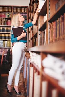 Donna che cerca un libro in biblioteca