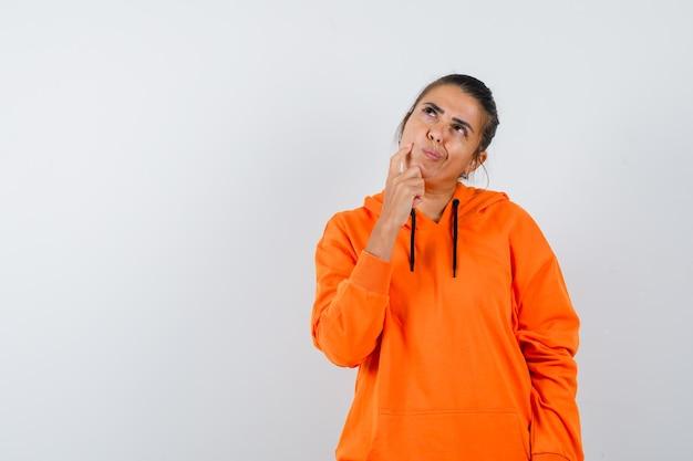 オレンジ色のパーカーで考えながら見上げる女性とインテリジェントに見える