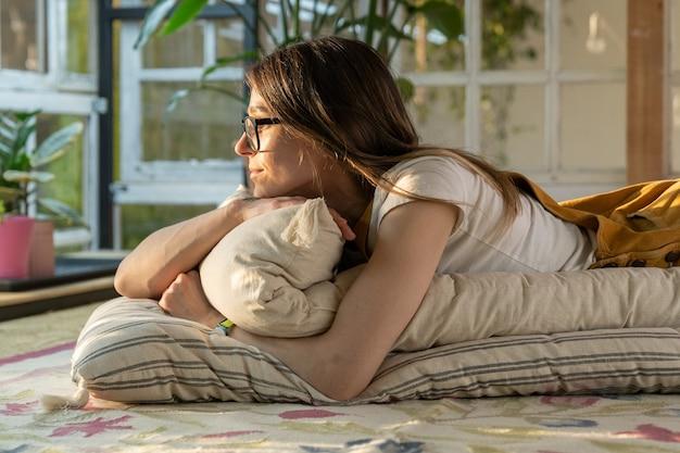 リラックスしたリビングルームの床のマットレスの上に横たわっている女性