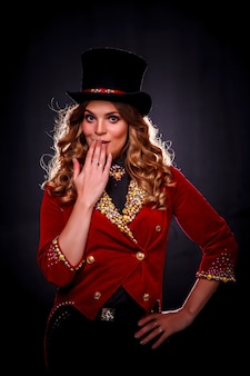 Female magician an illusionist in performance clothes, woman actress show emotion on black background
