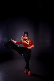 Female magician, an illusionist in theatrical clothing, shows magic ball and black mantle on black background. man in stage costume and top hat on her head. concept of theatrical performance