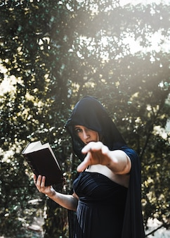 Female magicianpractising witchcraft in sunlit forest