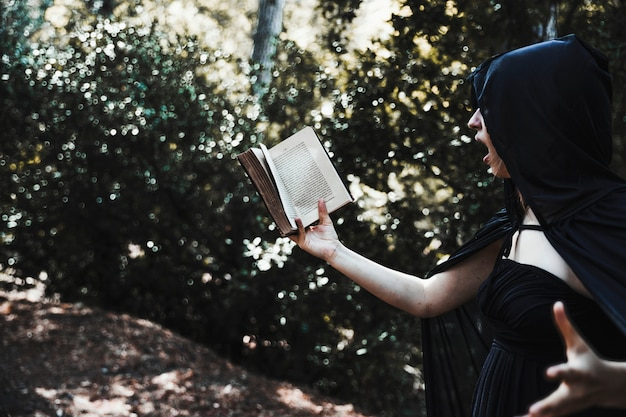 Female magician reading spell inthicket