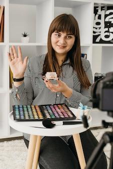Blogger di trucco femminile con streaming a casa con fotocamera