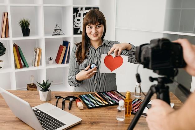 Blogger di trucco femminile con streaming con fotocamera e laptop a casa