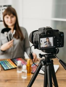 Blogger di trucco femminile con streaming con fotocamera