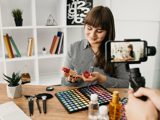 Женский макияж блоггер с потоковой передачей со смартфоном дома