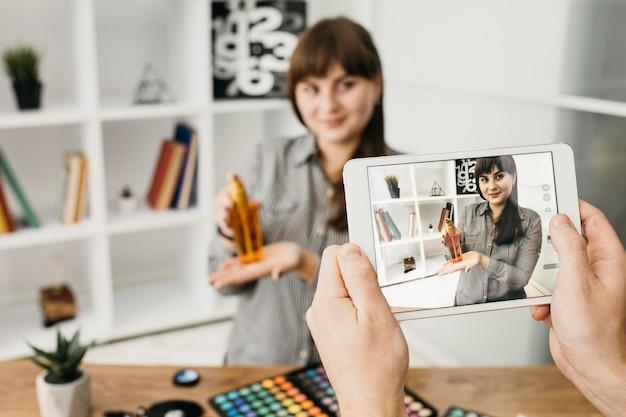 태블릿으로 스트리밍하는 여성 메이크업 블로거