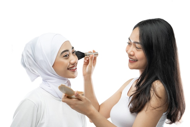 Female makeup artist applying cheek with brush of young muslim woman in hijab