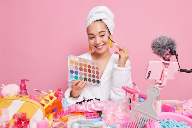 여성 메이크업 아티스트는 다양한 화장품으로 둘러싸인 집에서 청중에게 온라인으로 아이섀도우 팔레트 기록 라이브 스트리밍을 보여주며 매일 메이크업을 하는 방법을 보여줍니다. 인플루언서 블로거