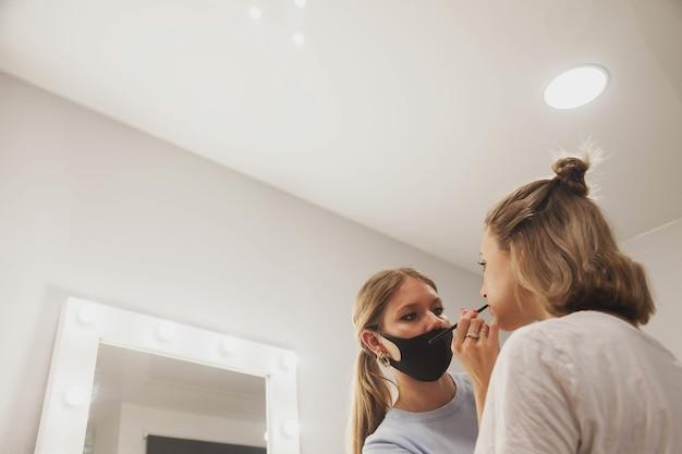 Женский визажист составляет симпатичную молодую женщину в салоне красоты. обслуживание клиентов в салоне интерьера для создания потрясающего имиджа. мастер создания рабочего макияжа. понятие меры удовлетворенности. копировать пространство