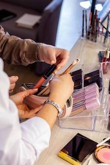 Визажист-женщина разбирает косметичку клиента, обучающего выбору кистей и блеска для губ