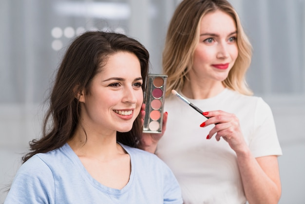 Female makeup artist showing stylish eyeshadow palette