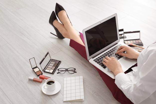 Женский визажист с ноутбуком и косметикой дома