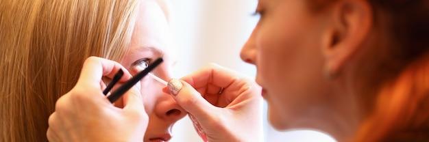 Женский визажист работает с глазами женской модели. салонная процедура, порошковая техника. создает эффект тонированные брови или карандаши с тенями. техника макияжа подходит для любого типа кожи