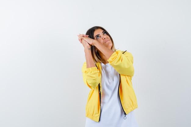 Donna che fa il segno della pistola del dito in maglietta, giacca e che sembra sicura, vista frontale.