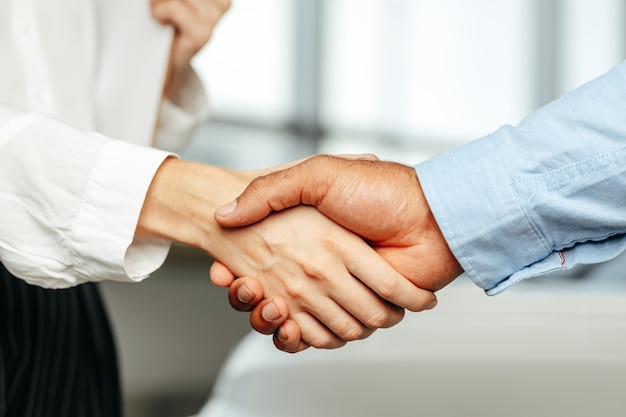 Female and male businesspeople handshake close up