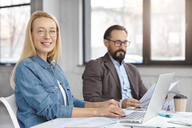 Gli economisti donne e uomini lavorano con documenti e tecnologie moderne