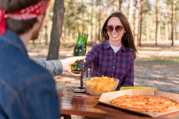 Female and male friends toast with beer over pizza