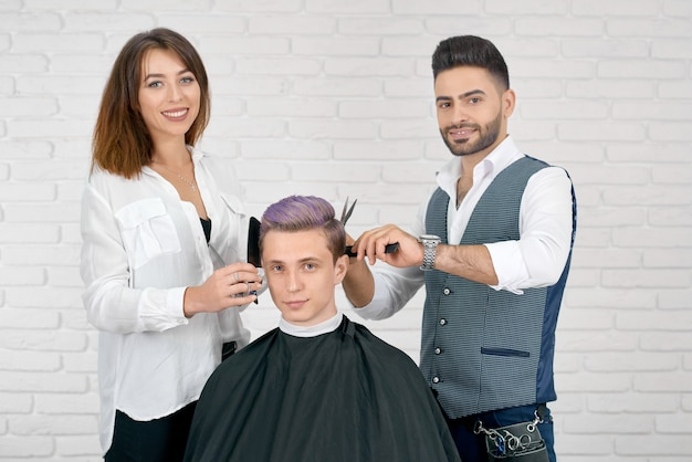 Female and male hairstylists doing haircut for young client with toned hair.
