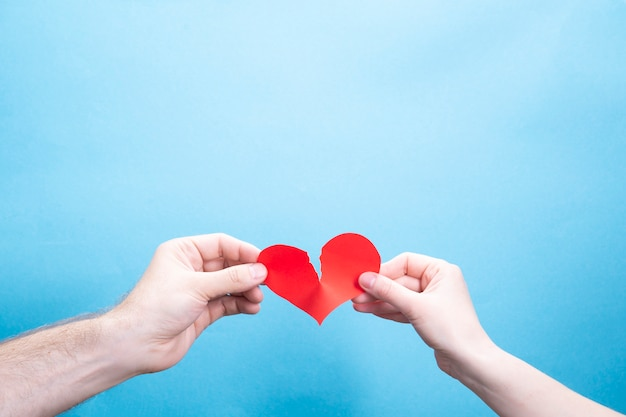 Female and male hand break a paper red heart on a blue