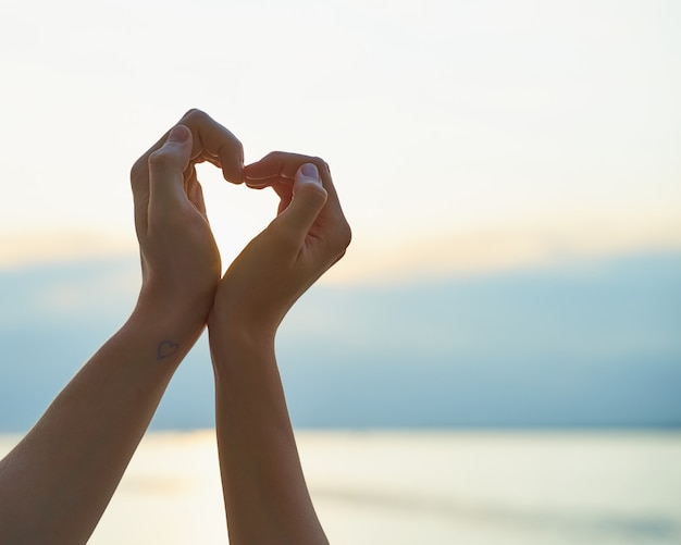 Female and male hand showing heart, symbol of love, beach background