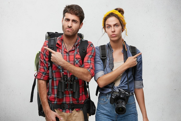 Female and male hitch-hikers holding huge baggage in their rucksacks, binoculars and camera for making various photos, pointing with their fingers in different sides not knowing where to go better