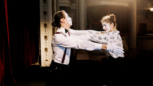 Female and male mime artist trying to hug each other on stage