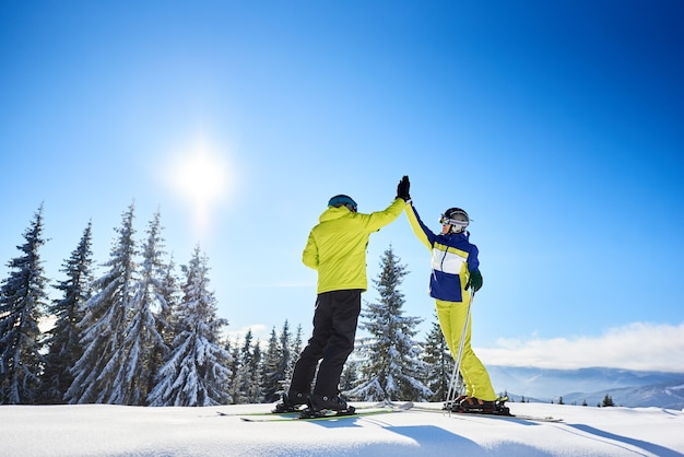 Female and male skiers high five to each other under sunny blue sky