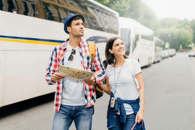 Female and male tourists walking near buses, holding map in hands, while searching for hotel where to stay. energetic travelers searching for location in unknown place. people, exploration concept