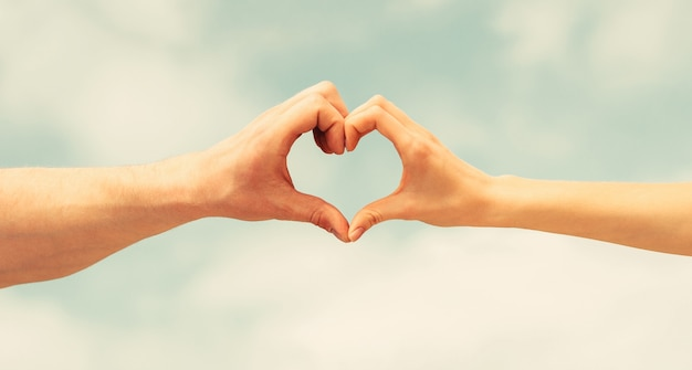 Female and man hands in the form of heart against the sky. hands in shape of love heart. heart from hands on a sky.