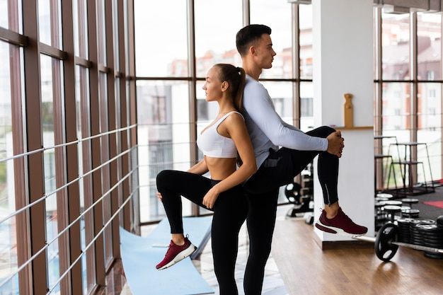 Female and man mirroring exercise at gym