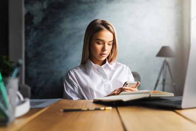 스마트 폰 및 회사 주소록을 사용하여 고객에게 전화하는 여성 관리자