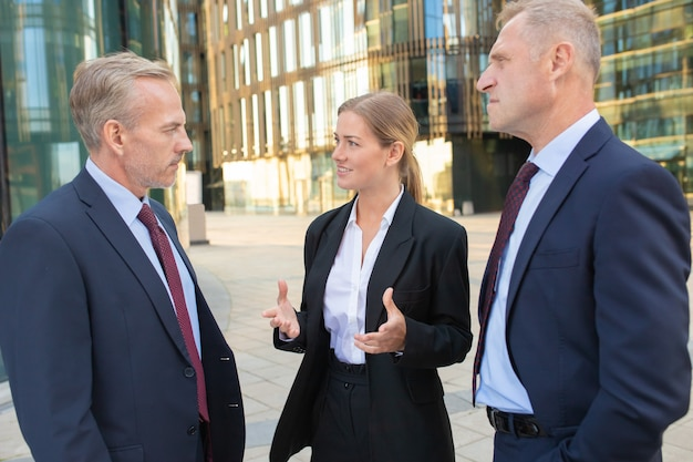 Female manager discussing deal with serious customers. businesspeople wearing suits, standing and talking outdoors with city building in background. meeting and cooperation concept