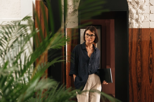 Female manager in eyeglasses with folder in hand