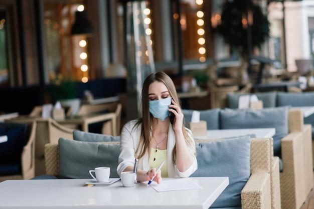 Женщина-менеджер в костюме и медицинской маске удаленно работает в уличном кафе