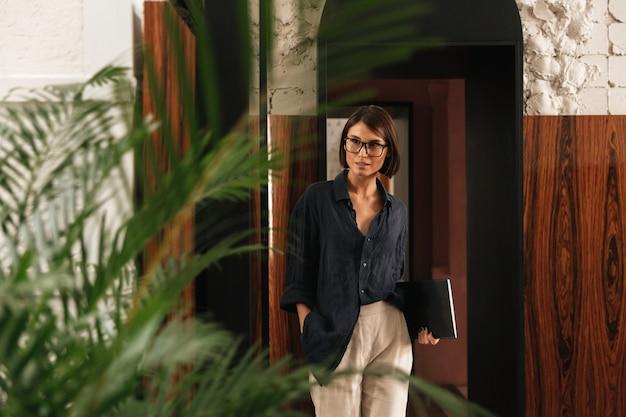 Женский менеджер в очках с папкой в руках