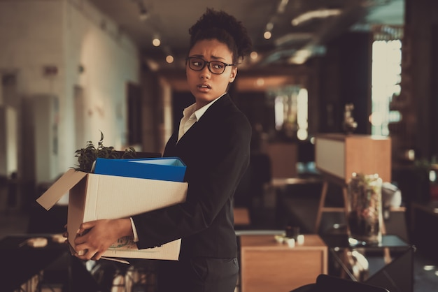 Female manager leaves workplace with office box.