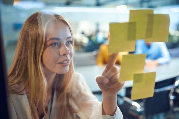 여성 관리자는 알림 시트, it 사무실을 살펴봅니다. 전문 작업자, 계획 또는 브레인스토밍. 성공적인 사업가는 현대 회사에서 일한다