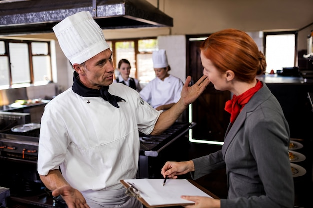 Female manager and male chef interacting with each other in kitchen