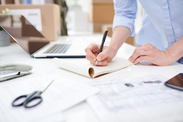 机のそばに立っている間ノートの空白のページにメモを作成するオンラインショップの女性マネージャー
