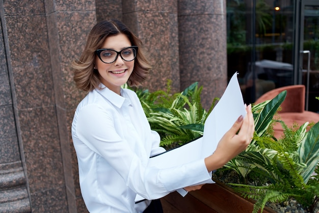 手にドキュメントを分離された背景を持つ屋外の女性マネージャー