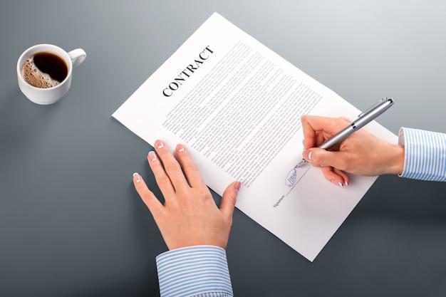 여성 매니저 서명 계약. 여자는 계약에 서명을 넣습니다. 우리 사무실의 아침. 조건에 만족합니다.