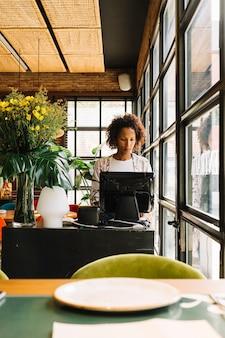 컴퓨터를 사용하여 그녀의 식당에 서있는 여성 관리자