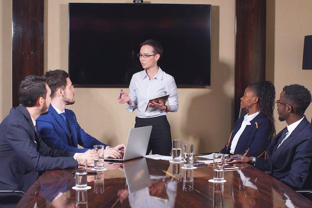 ビジネスミーティングでチームに対処するために立っている女性マネージャー。