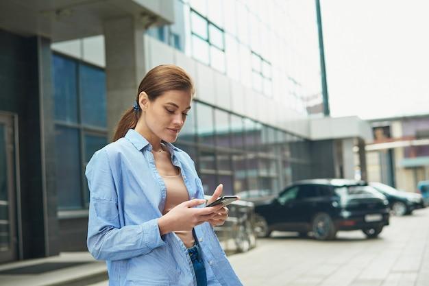 Женщина-менеджер использует мобильный телефон в городе на открытом воздухе, женщины в синей рубашке и джинсах пишет сообщение на мобильный. счастливая бизнес-леди в чате по телефону.